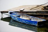 stock photo of dock a pond  - Old small blue boat abandoned in a dock - JPG