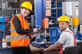 stock photo of production  - Production worker at workplace and his supervisor - JPG