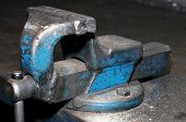 stock photo of workbench  - Blue clamp in a workbench installed in a workshop - JPG