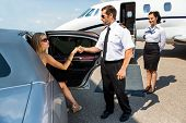 picture of diva  - Full length of pilot helping elegant woman stepping out of car at airport terminal - JPG