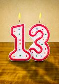 Burning birthday candles number 13 on a wooden background