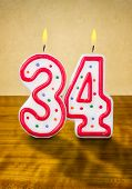 Burning birthday candles number 34 on a wooden background