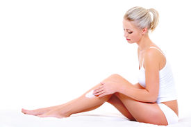 picture of body-lotion  - Beautiful pretty woman sitting on bed applying moisturizer cream on her slim legs - JPG