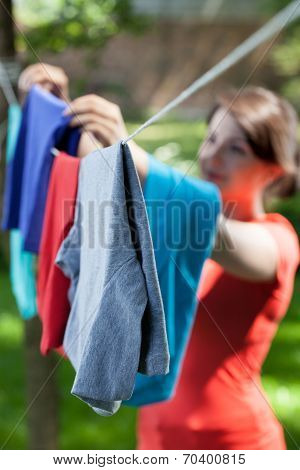 Woman Hanging Clothes On Laundry Line In Garden