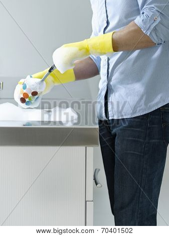 Side view of a midsection man doing washing up at kitchen sink