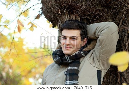 Young smiling man portrait in autumn park.
