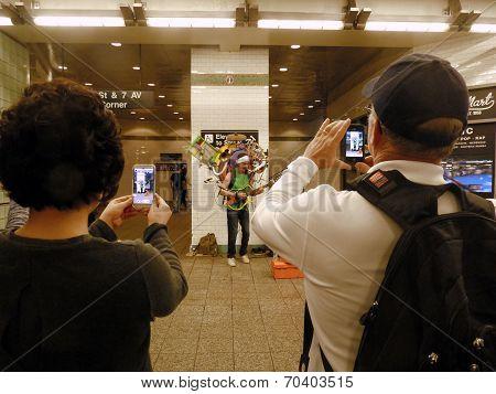 Tourists photograph busker