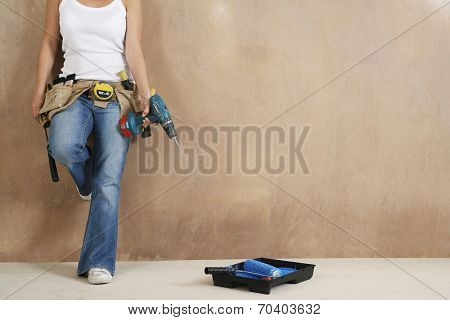 Lowsection of a young woman with toolbelt and drill leaning against wall