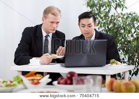 Businessmen Working And Eating Lunch