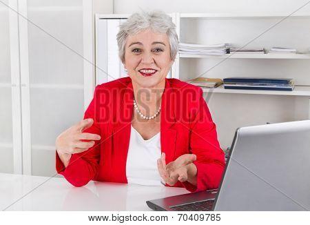 Attractive Older Smiling Senior Businesswoman Sitting At Desk Wearing Red Jacket.