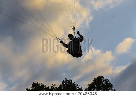 A paraglider soars in the sky at sunset