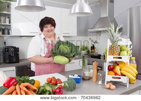 Chubby Smiling Woman In The Kitchen Making Diet.
