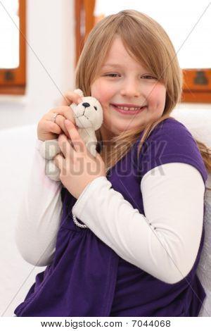 Little Girl With Teddy Bear On Sofa