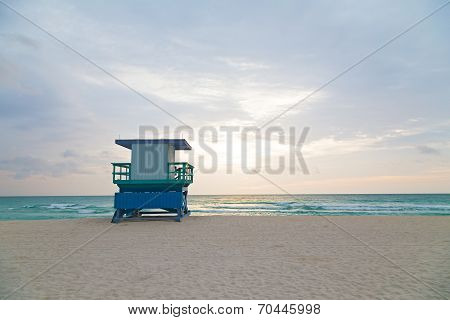 Empty beach with lifeguard cabin at sunrise.