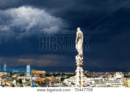 A statue of the Dome of Milan cathedral with the city view before the thunder.