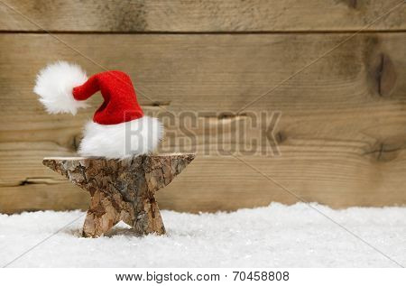 Wooden Star With Santa Hat On Wooden Background