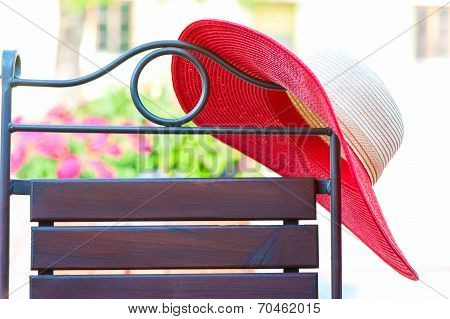 Part Of Elegant Metal Curved Chair And Red Summer Hat On Patio.