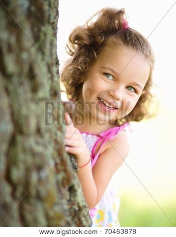 Cute little girl is playing hide and seek, outdoor shoot