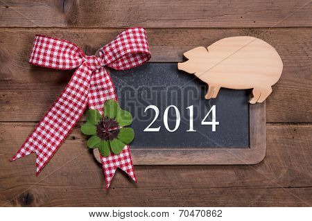 Happy New Year 2014 - Greeting Card On A Wooden Background With A Lucky Pig And A Green Clover With