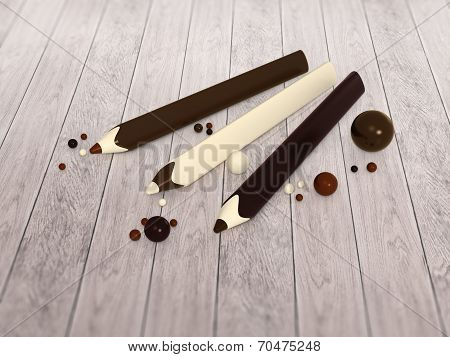 Chocolate Pencils And Balls On Wooden Floor