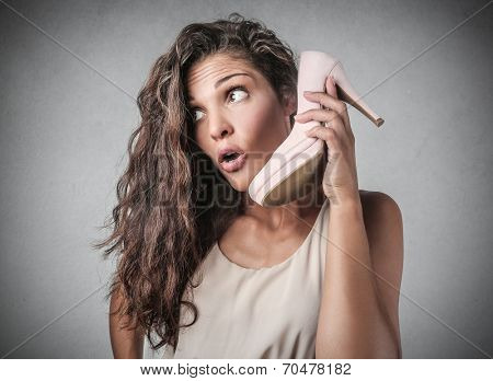young woman looking surprised, holding an high heeled shoe in her hand as a phone
