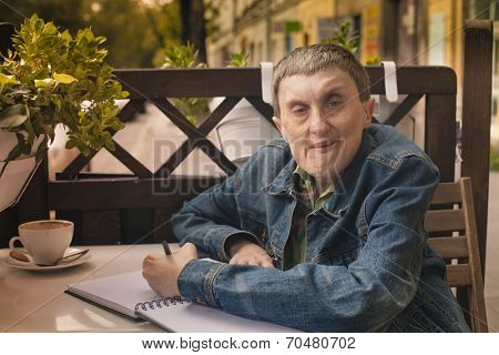 Disabled man with cerebral palsy writing in a notebook sitting at an outdoor cafe.