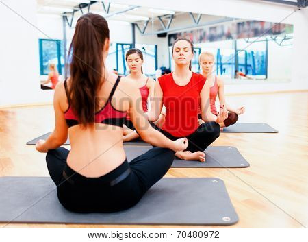 fitness, sport, training, gym and lifestyle concept - group of smiling female with trainer infront meditating in the gym
