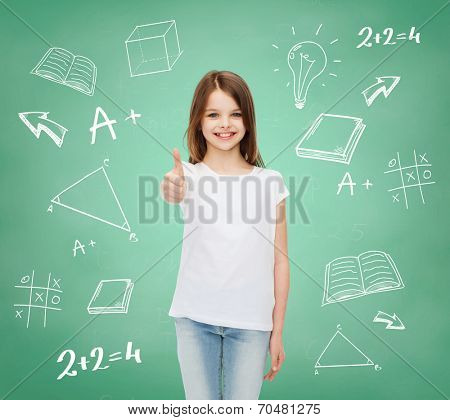 advertising, gesture, education, childhood and people - smiling little girl in white t-shirt showing thumbs up over green board with doodles background