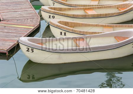 Numbered Pleasure Rowing Boats Tied Up On A Lake
