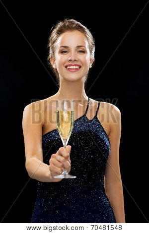 people, holidays, luxury and celebration concept - smiling woman holding glass of sparkling wine over black background
