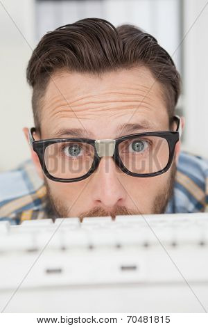 Puzzled nerdy businessman working on computer in his office