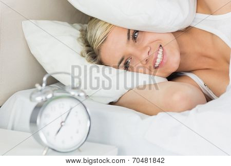 Beautiful young woman an covering ears with pillow as she looks at alarm clock in bed