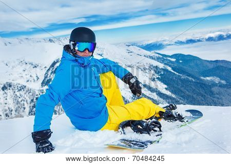 Snowboarder sitting on the snow slope