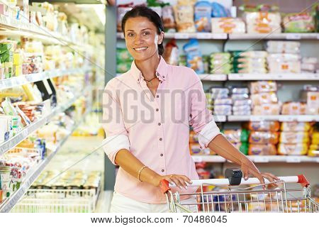 woman during shopping at supermarket with cart trolley