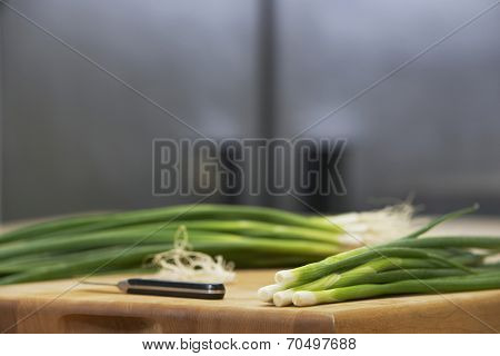 Closeup of fresh spring onions and knife on chopping board