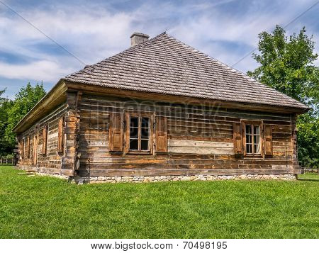 Old style wooden cottage with window shutters