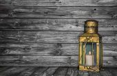 stock photo of deceased  - Old rustic golden copper lantern on wooden old shabby background for concepts - JPG