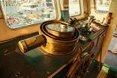 image of ship steering wheel  - Old ancient steering wheel of copper in the cockpit of an old antique ship - JPG