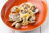 stock photo of clam  - Seafood pasta with clams Spaghetti alle Vongole on orange plate - JPG