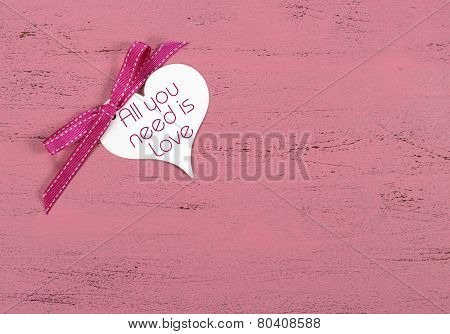Valentine Greeting Heart Shape Gift Tag With All You Need Is Love Sample Text On Pink Wood Table.