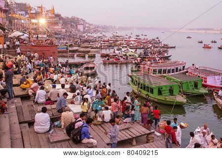 VARANASI, INDIA - MARCH 20, 2013: Boats and people on the ghats on the banks of Ganges river in holy city of Varanasi on March 20, 2013 in Varanasi, Uttar Pradesh, India.