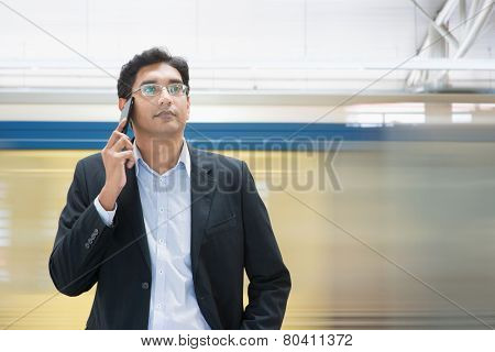 Asian Indian businessman on the phone while waiting train at railway station.