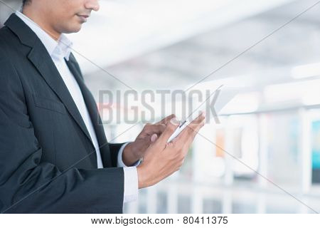 Asian Indian business people using tablet computer while waiting train at railway station.