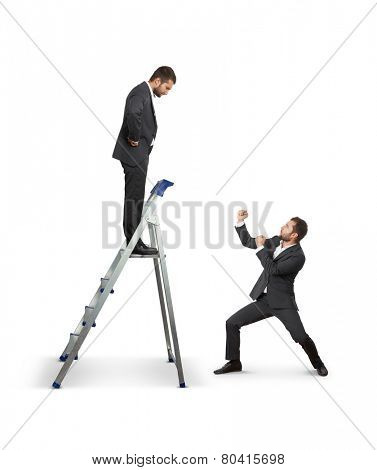 serious man on the stepladder looking down on businessman in fighting stance. isolated on white background