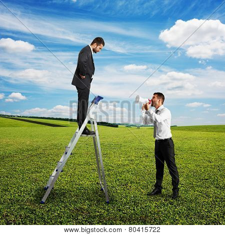 angry man with megaphone screaming at man on the stepladder at outdoor