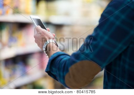 Man Using Mobile Phone While Shopping In Supermarket
