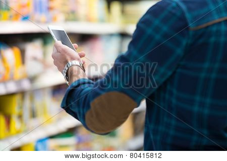 Man Looking At Mobile Phone In Shopping Centre