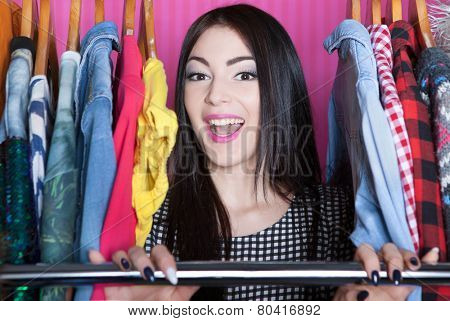 Young attractive laughing woman searching for clothing in a closet