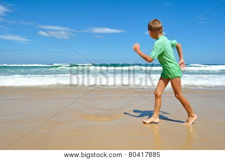 Young Boy Walking Along The Beach
