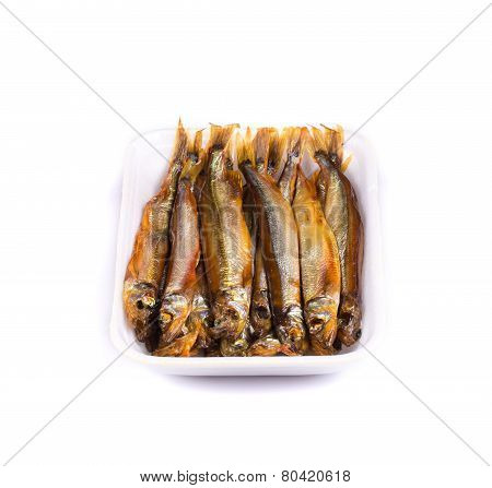 Smoke-dried anchovies in plate close up.